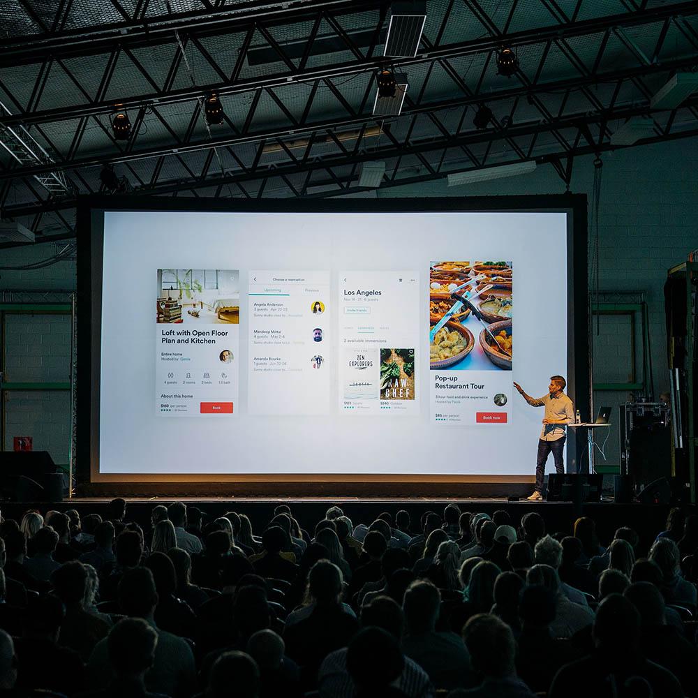 Mann på scene med infoskjerm storskjerm