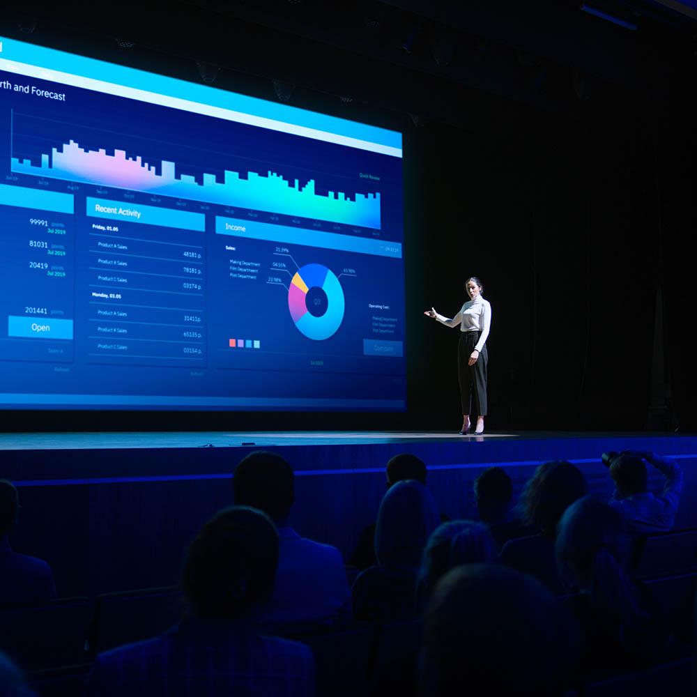 Kvinne på scene med infoskjerm