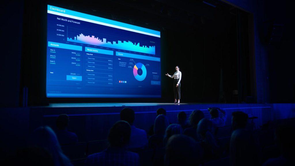 Kvinne på scene med infoskjerm storskjerm